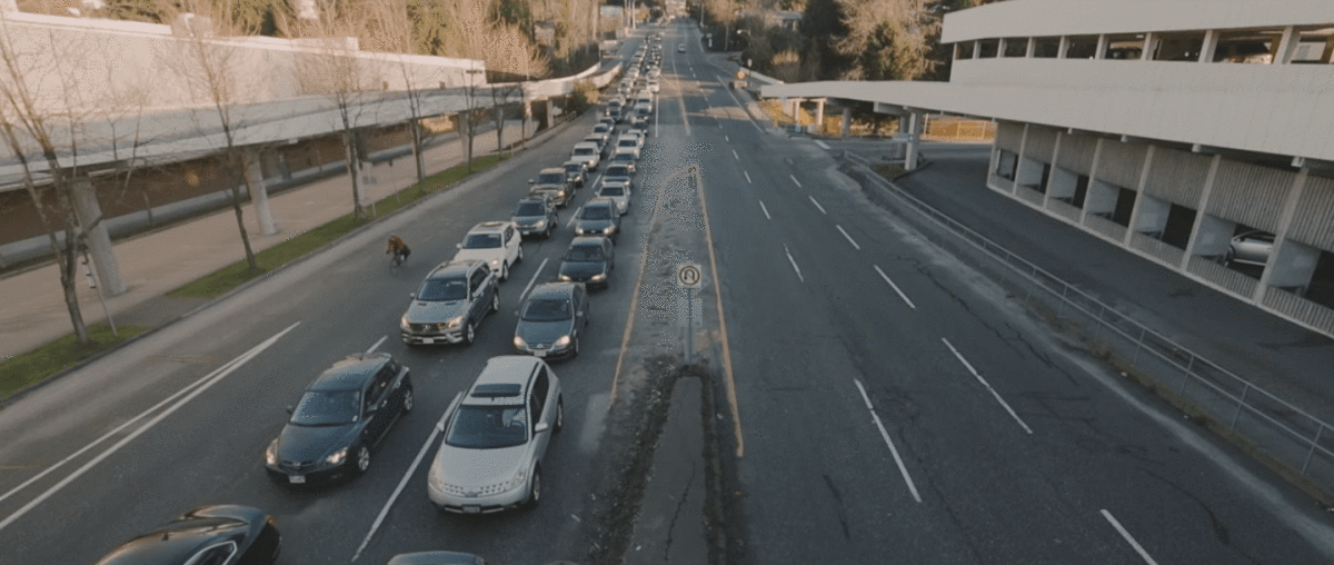 A Cyclist Passes by Cars Stuck in Traffic