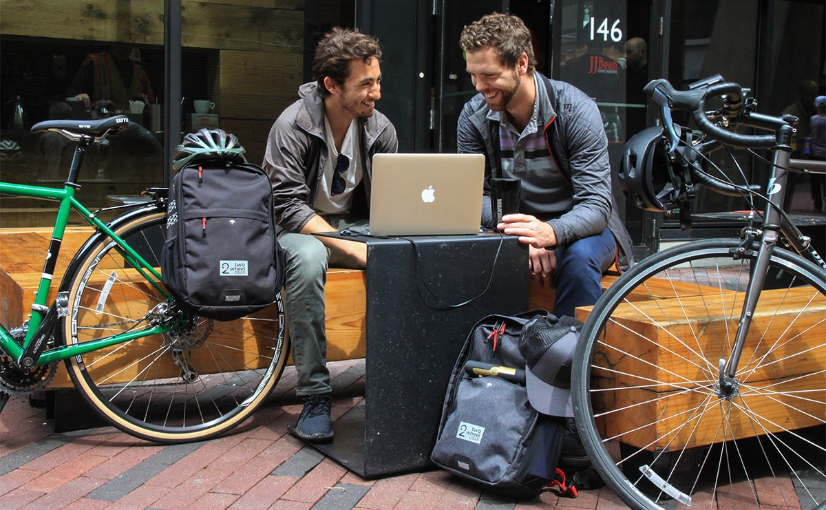 Two Cyclists Laugh and Chat During Lunch Break