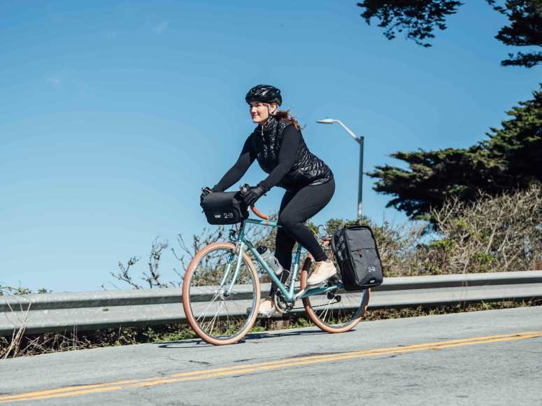 Two Wheel Gear - Woman commuting on bicycle with Mini Messenger Handlebar Bag and Pannier Backpack Convertible.